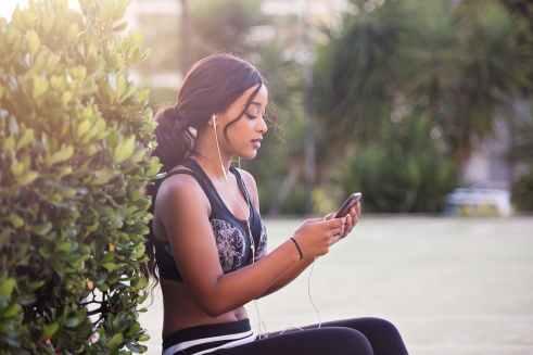 woman in black crop top holding smartphone